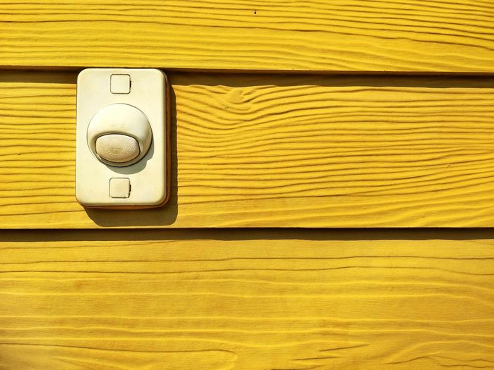 The old electric bell on wooden yellow wall background in home decorations concept Buzzer Electric Wall Wooden Paint Old Decoration Home House Warning Sunlight And Shadow Surface EyeEm Selects Yellow Backgrounds Close-up Architecture Built Structure Yellow Background Wooden Plank Door Switch