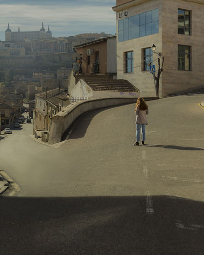 Rear view of woman standing by buildings in city