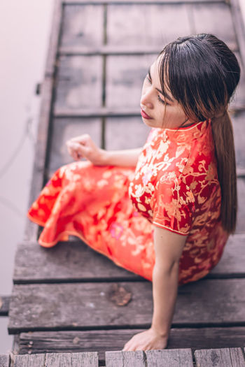 Woman looking away while sitting outdoors
