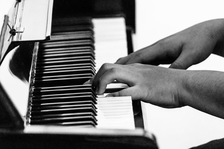 Close-up of man hands playing piano