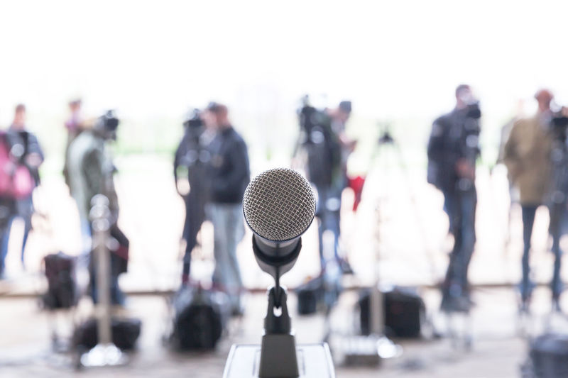 Microphone in focus against blurred camera operators and reporters at press conference Focus Unrecognizable People Microphone Mic Reporter Reporting Report News Information Journalism Journalist Media Media Equipment Media Event The Media Broadcasting Broadcasting Journalism Recording Record Speech News Conference Press Conference Public Relations Publicity CameraMan Audio Video Camera Tv Tv Camera Close-up Close Up Asking Question Audio Equipment Camera Operator Speak Out Public Public Event Event Communication Operator