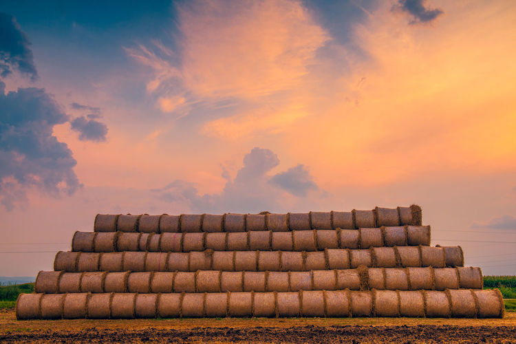 Stack of stones on field against sky during sunset