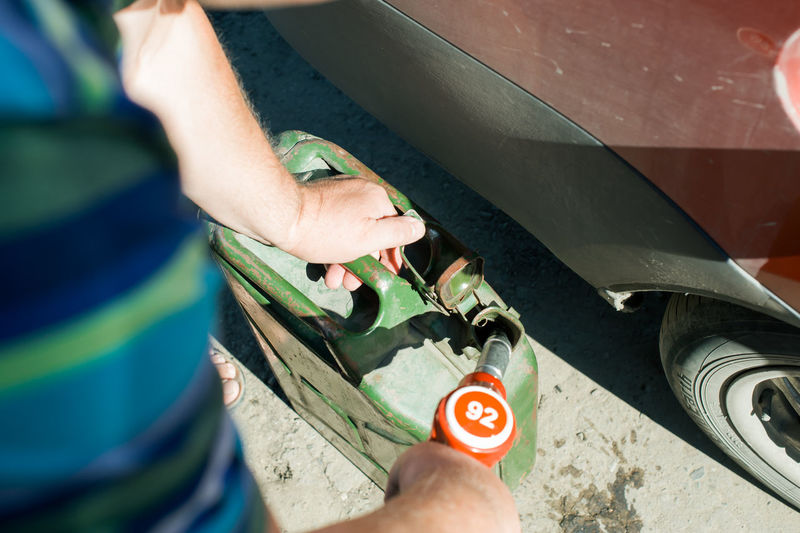 Cropped Image Of Man Filling Gasoline In Container