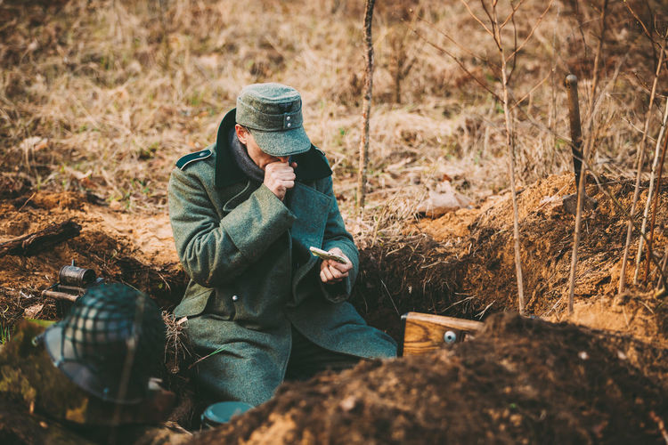 Pribor, Belarus - April, 04, 2015: Unidentified Re-enactor Dressed As World War German Wehrmacht Soldier In A Trench Settling For Night Men Field Pribor Belarus Re-enactors World War Wehrmacht Soldier WWII Ww2 Trench Army Front German Historic Military Reconstruction Tree
