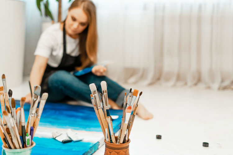 Close-up of paintbrushes with woman painting in background at home