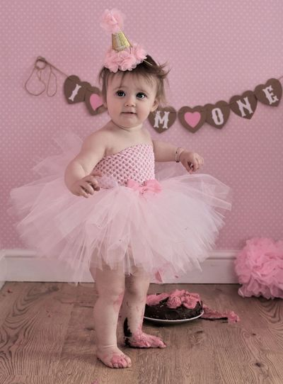 Messy Baby Girl In Dress Standing By Birthday Cake At Home