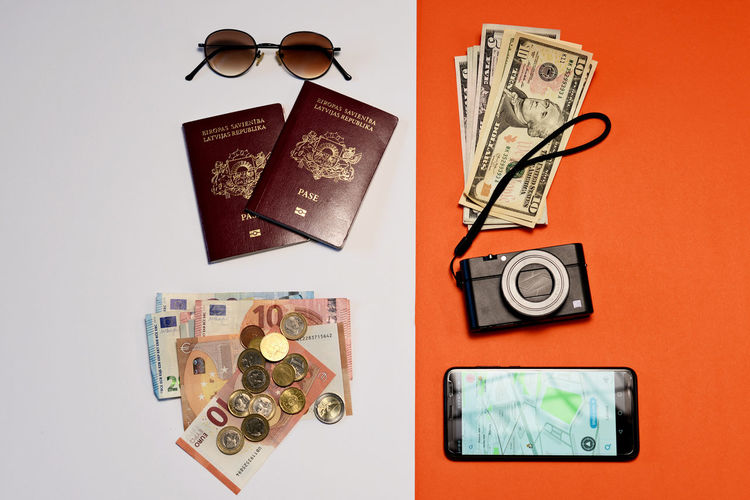 Sunglasses, smartphone, passports, camera and money on a white and orange paper background. Tourism concept. Dollar Money Cash Savings Banking Finance Bill Currency Wealth Background Banknote Bussiness Profit Green Close-up USD Exchange Loan  Paper Sign Payment Pay Stack Number Textured  Abstract Earnings Symbol Capital Assets Sunglasses Camera Phone Smart Phone Passports Passport Navigation Euro Coins Tourism Travel Concept Isolated Indoors  Technology Still Life No People Directly Above Studio Shot Communication Table Paper Currency Connection Variation Large Group Of Objects High Angle View Choice Wireless Technology Arrangement