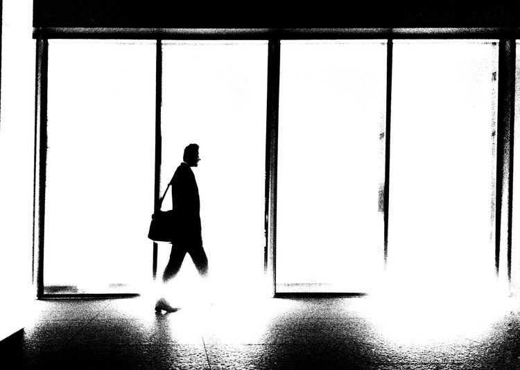 Silhouette man standing by window of building