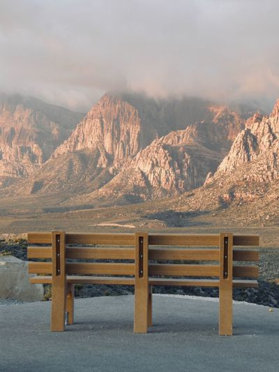 Empty bench on mountain during sunset