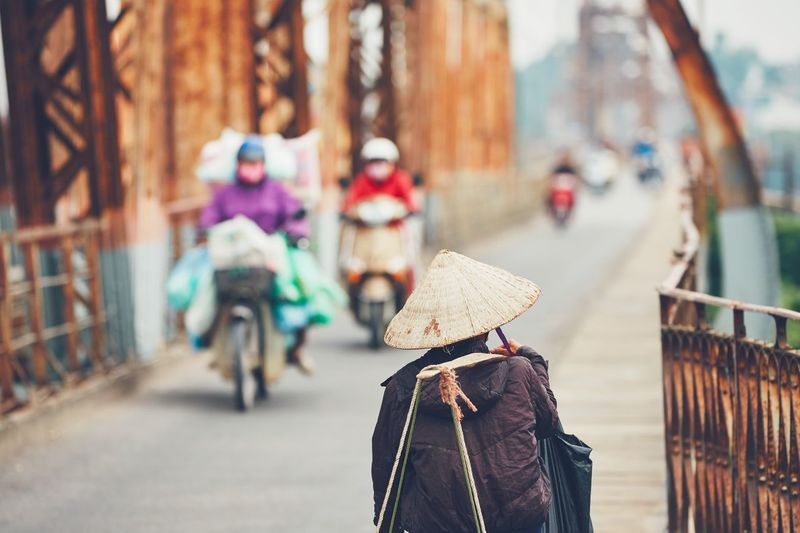 Vietnamese street vendor is carrying lots of stuff across Long Bien Bridge in Hanoi, Vietnam. Selective focus on the traditional hat. City City Life Motorcycle Traditional Culture Traffic Transportation Travel Trip Vietnam Asian Style Conical Hat Bridge Hanoi Hat Motorbike Outdoors Pedestrian People Real People Rear View Street Streetphotography Traditional Travel Destinations Walking