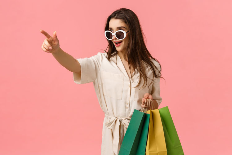 Woman wearing sunglasses standing against pink background