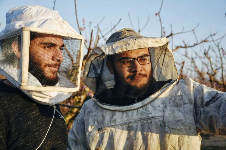 Portrait of two friends wearing special costumes to protect them from bees
