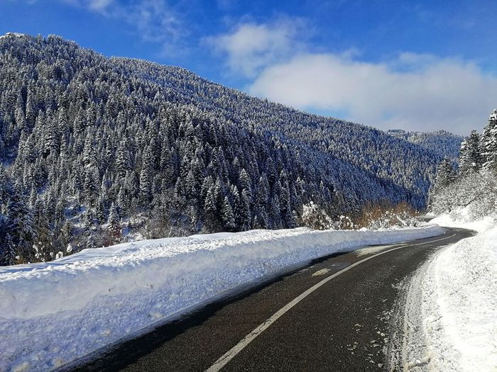 Road by snowcapped mountain against sky
