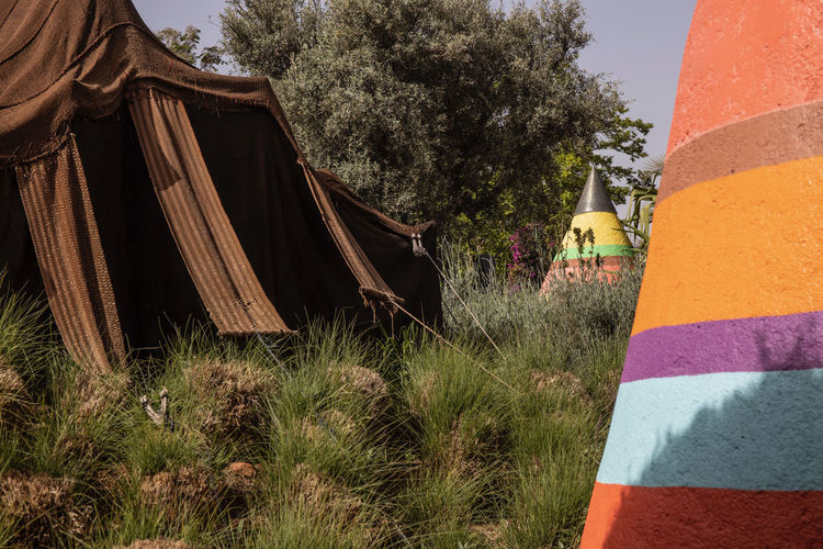 a very imaginative garden space outside of Marrakech, Morocco with beautiful and colourful objects blending with the garden Garden Park Colorful ArtWork Trees Path Imaginative Marrakech Morocco Anima Garden Textured  Plant Tree Grass Nature Architecture No People Built Structure Day Land Building Exterior Field Outdoors Growth Textile Multi Colored Sky Building Tranquility Wood - Material Striped