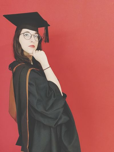 Woman In Graduation Gown Posing By Red Background