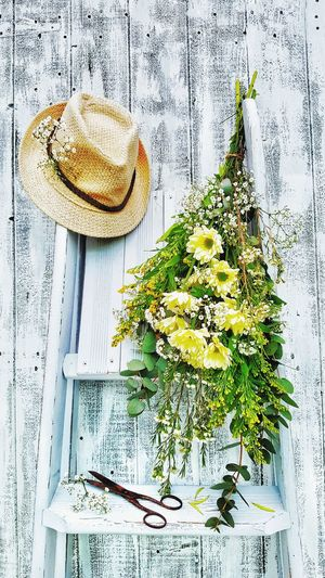 Flowers and hat on ladder against wooden wall