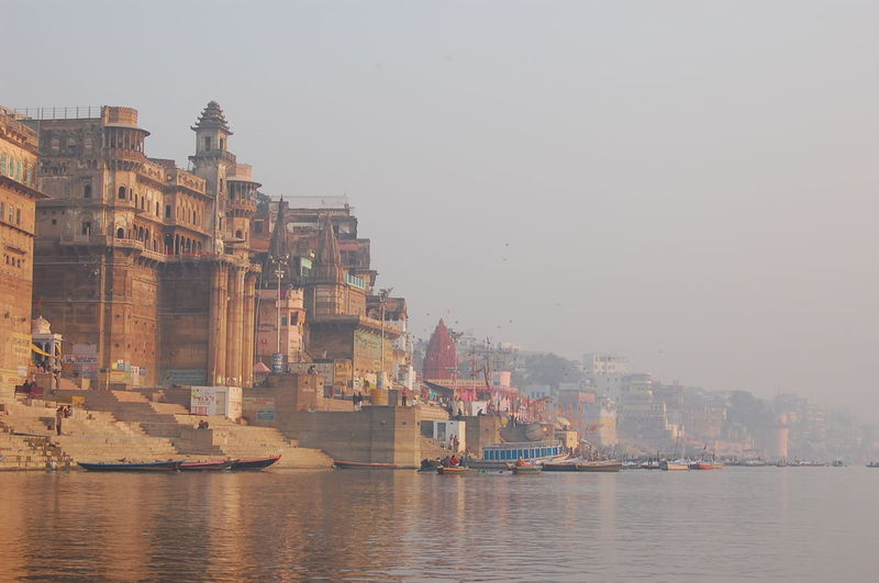 Temples By Ganges River Against Sky During Foggy Weather