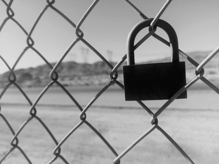 Close-Up Of Lock Attached On Chainlink Fence At Desert