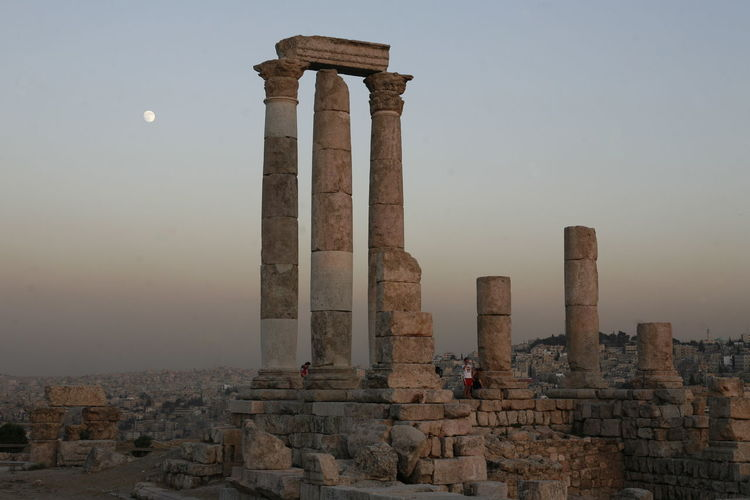 Low angle view of amman citadel seen from cave against sky during sunset