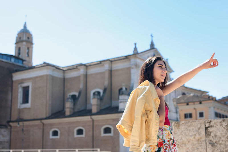 Low angle view of beautiful woman pointing by church against clear sky