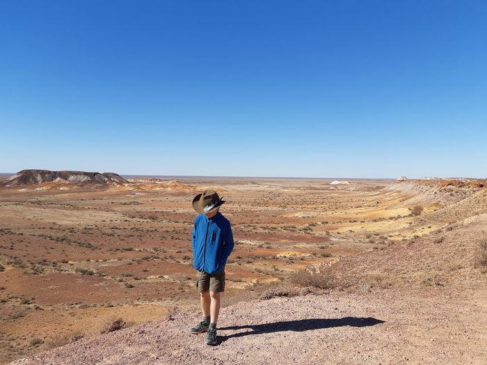 Full length of boy walking on landscape against clear blue sky