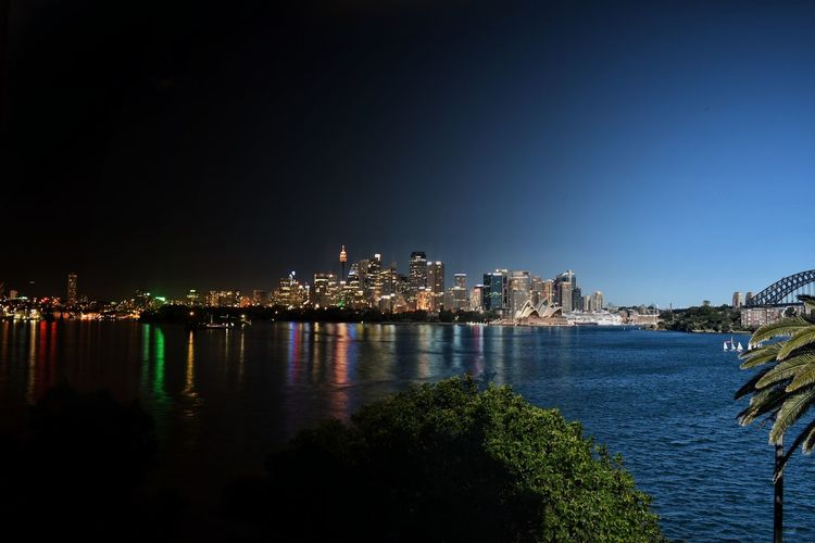 Sea Cityscape Night City Skyscraper Illuminated Architecture Travel Destinations Urban Skyline Building Exterior Outdoors Blue Water No People Clear Sky Sky Scenics Day Day And Night