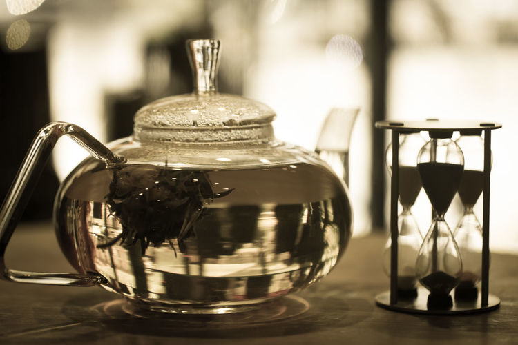 Close-up of herbal tea in pot by hourglass on table
