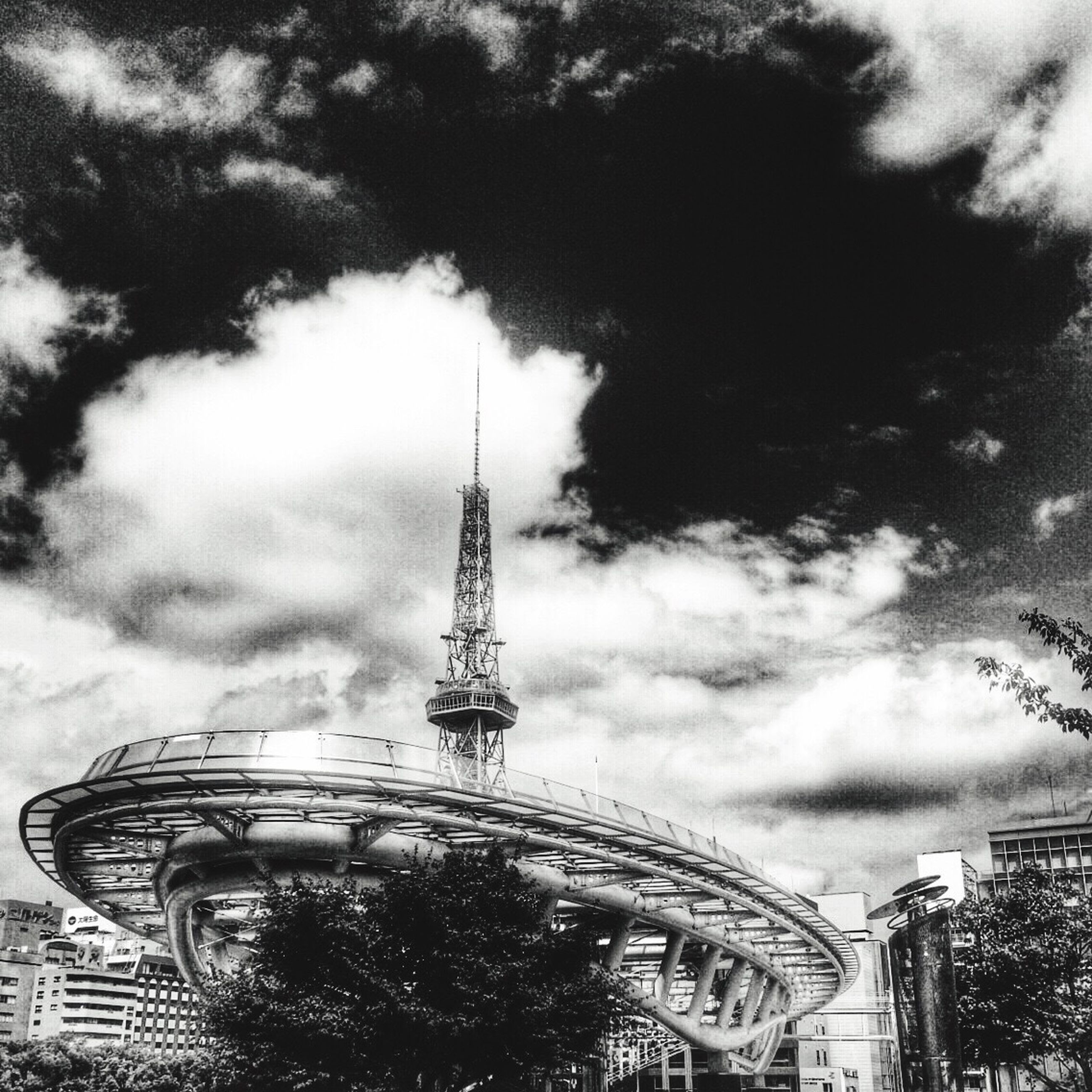 low angle view, sky, built structure, architecture, tower, cloud - sky, building exterior, cloudy, tall - high, travel destinations, famous place, international landmark, capital cities, tree, tourism, amusement park, travel, amusement park ride, city, communications tower