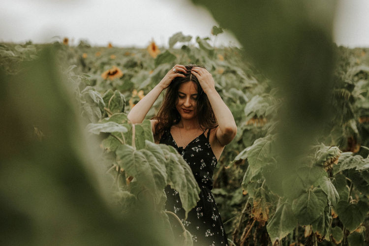 Young woman standing at sunflower farm