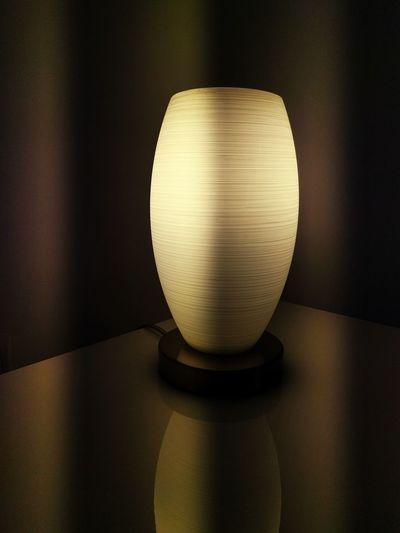 Close-up of illuminated lamp on table