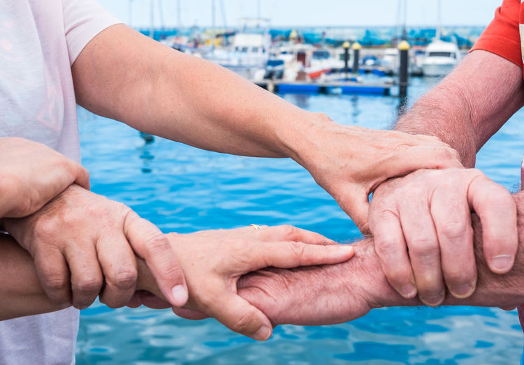 Midsection of senior friends holding hands while standing at harbor