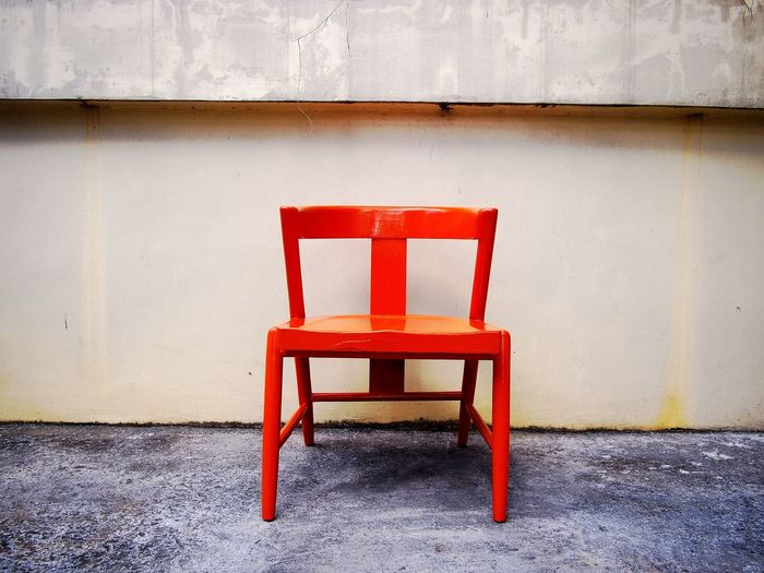 Empty red chair against retaining wall