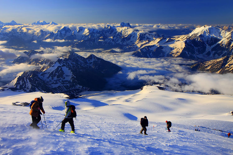 Hikers on snowcapped mountains against sky
