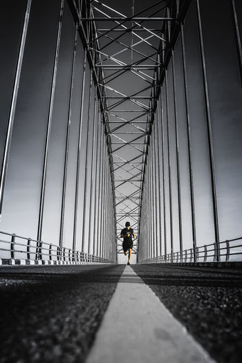 Silhouette person walking on bridge against sky