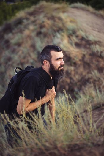 Portrait of a man with a tourist backpack with a beard on the background of nature and mountains