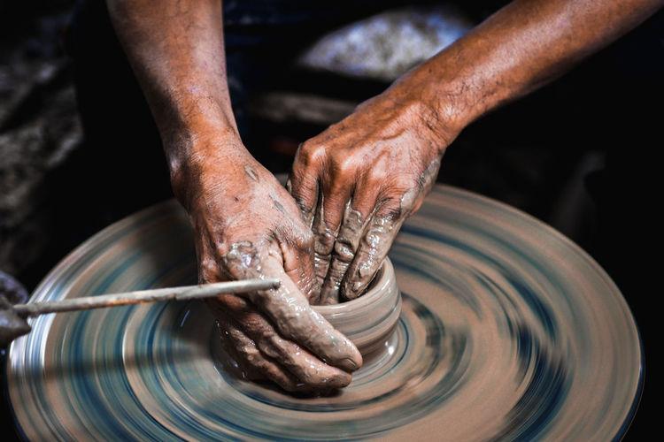 Close-up of artist making pot at workshop