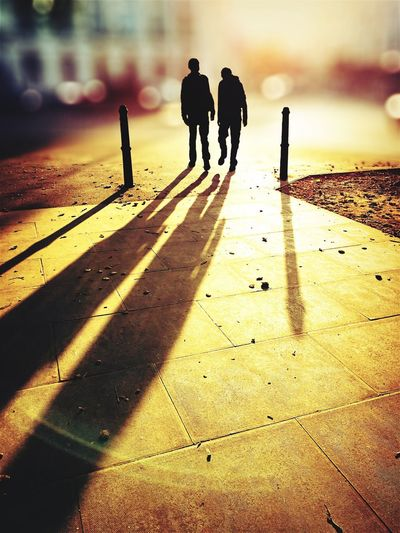 A pair of bollards Silhouette Men Shadow Rear View Auto Post Production Filter Silhouette Standing Togetherness Solitude Surface Level Outdoors Focus On Foreground Focus On Shadow Outline The Way Forward