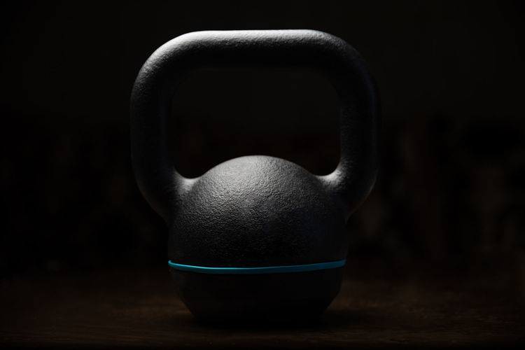 Close up view of a kettlebell - studio shot Dark Heavy Black Background Body Building Close-up Club Crossfit Dark Fit Fitness Focus On Foreground Gym Health Indoors  Kettlebell  No People Single Object Sport Spotlight Still Life Studio Shot Table Weight Wellbeing Wood - Material