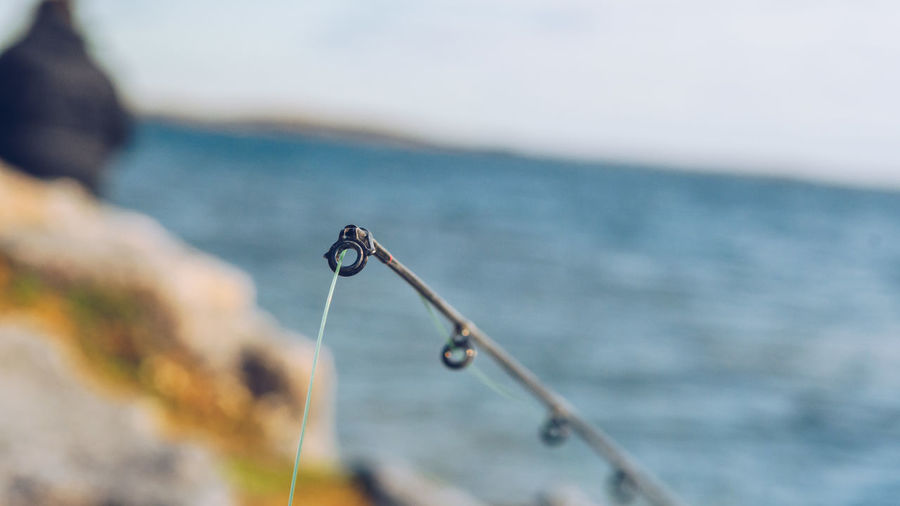 Close-up of fishing rod by sea against sky