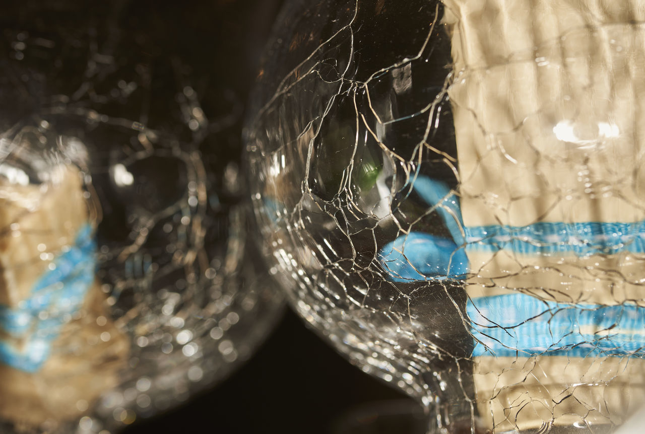 CLOSE-UP OF SPIDER WEB ON GLASS OF