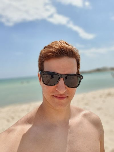 Portrait of shirtless man wearing sunglasses standing at beach
