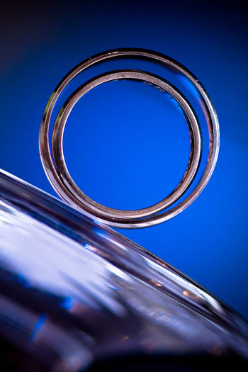 Blue Close-up No People Metal Blue Background Shiny Colored Background Geometric Shape Circle Shape Ring Glass - Material Still Life Selective Focus Wedding Rings Two Two Rings Wedding Rings Wedding Ring Rings 💍 Inside Inserted On The Edge Circles In Circles 50 Ways Of Seeing: Gratitude Capture Tomorrow