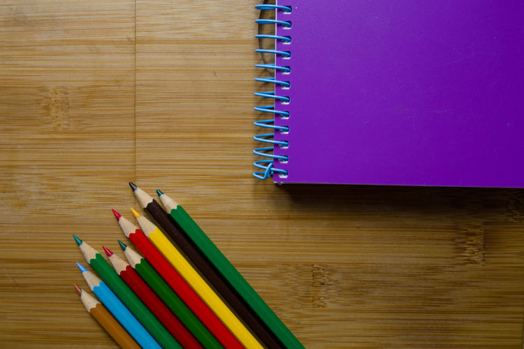 High angle view of colorful pencils with book on wooden table