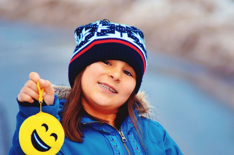 Portrait of smiling cute girl holding emoticon