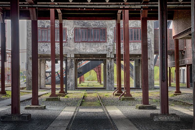 Metal Columns Against Old Building At Zollverein Coal Mine Industrial Complex