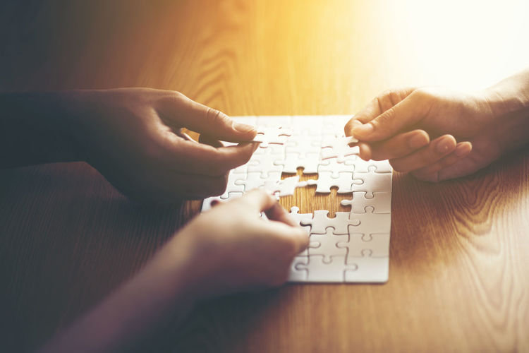 Midsection Of People Playing With Jigsaw Puzzle On Table