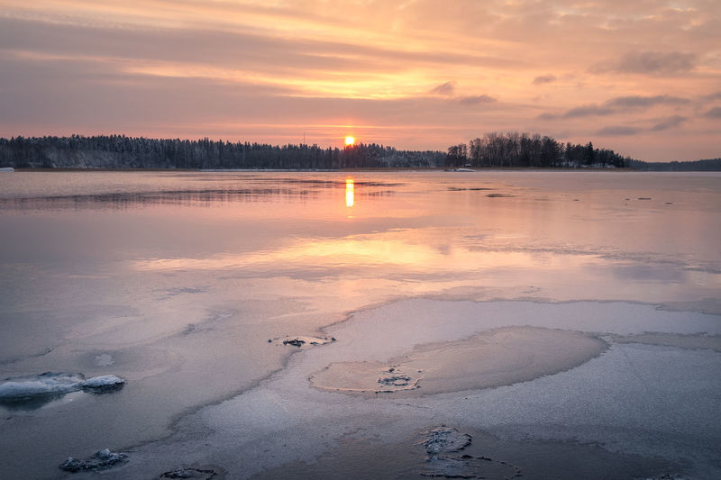 Scenic winter landscape with sunset and water reflections at evening time in Finland Sunset Sky Beauty In Nature Scenics - Nature Cloud - Sky Tranquility Tranquil Scene Water Winter Cold Temperature Frozen Orange Color Ice Snow No People Non-urban Scene Nature Reflection Sun Cold Finland Tranquility Moment Of Silence Peaceful Idyllic