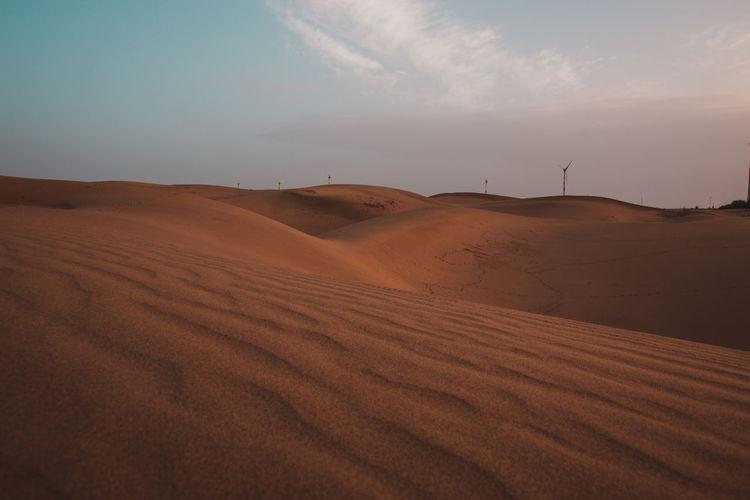Sand dunes in desert against sky