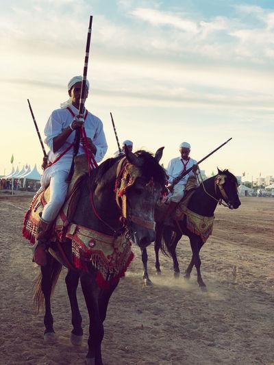 Men riding horses on street against sky
