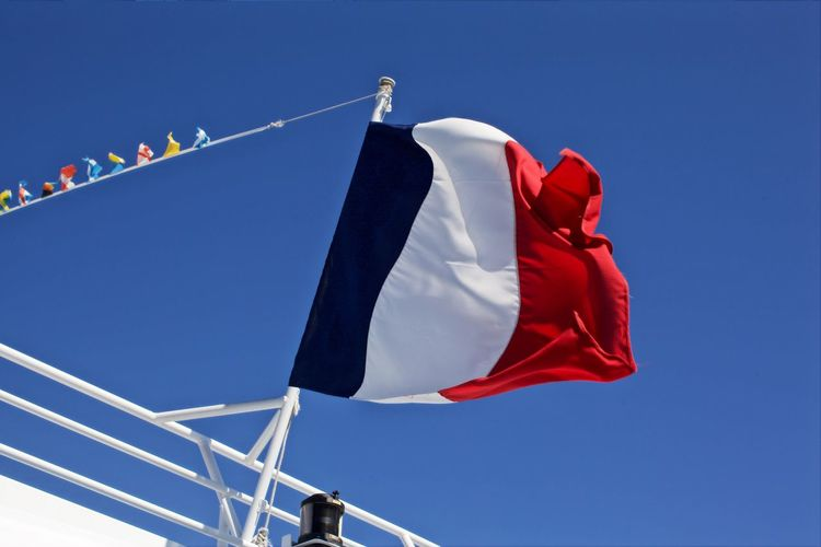 Low angle view of french flag on railing against clear blue sky